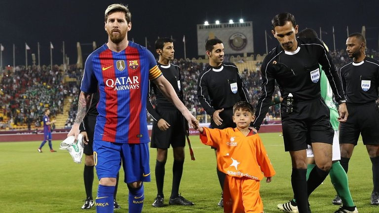 Lionel Messi holds the hands of Ahmadi on the pitch before a friendly
