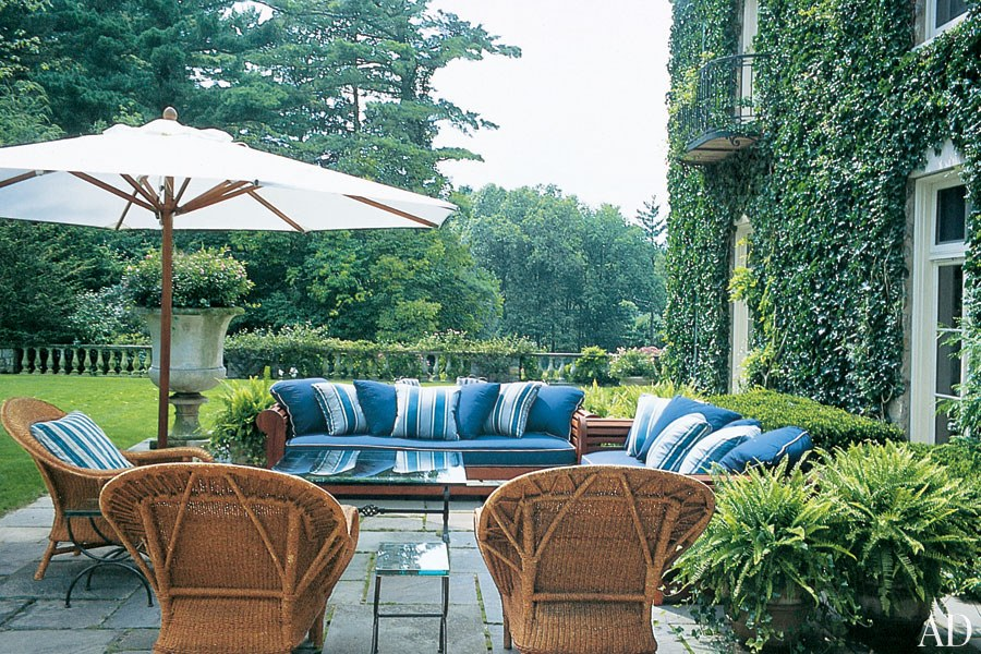 The rear terrace of Ralph and Ricky Lauren's ivy-covered home in Bedford, New York, features relaxed seating for entertaining and offers views of the 250-acre property's sprawling lawn. (November 2004)