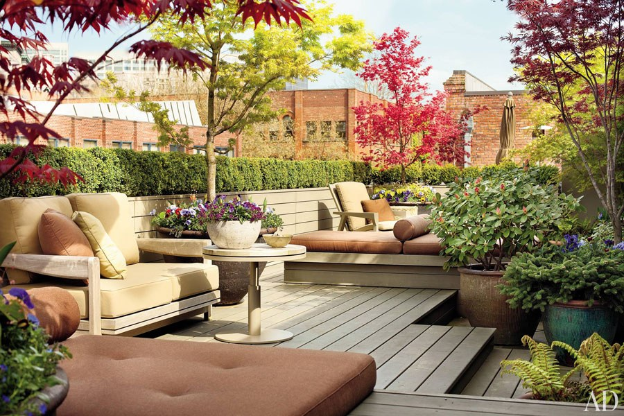 Overlooking the Seattle skyline and Elliot Bay, the 900-square-foot rooftop terrace of designer Terry Hunziker's Pioneer Square apartment is planted with vibrant Japanese maple trees and manicured shrubs.