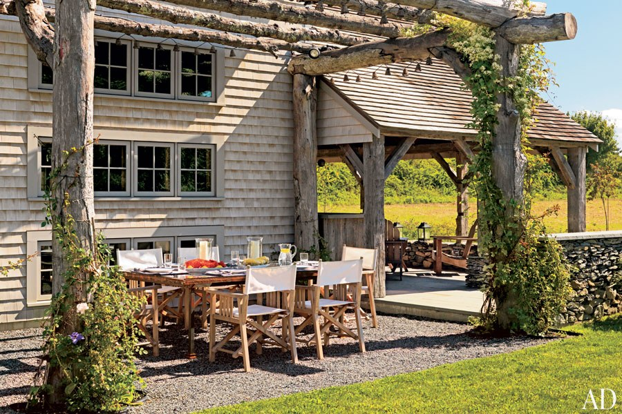 Flowering vines adorn the rustic log arbor surrounding the outdoor dining area of designer Ellen Denisevich-Grickis's Rhode Island retreat. Unmilled oak trees were used to create the structure, which spans almost the entire rear façade of the 18th-century barn.
